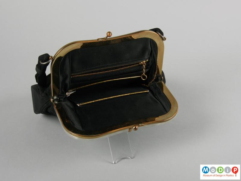 Side view of a handbag showing the clasp open, exposing the inner pockets.