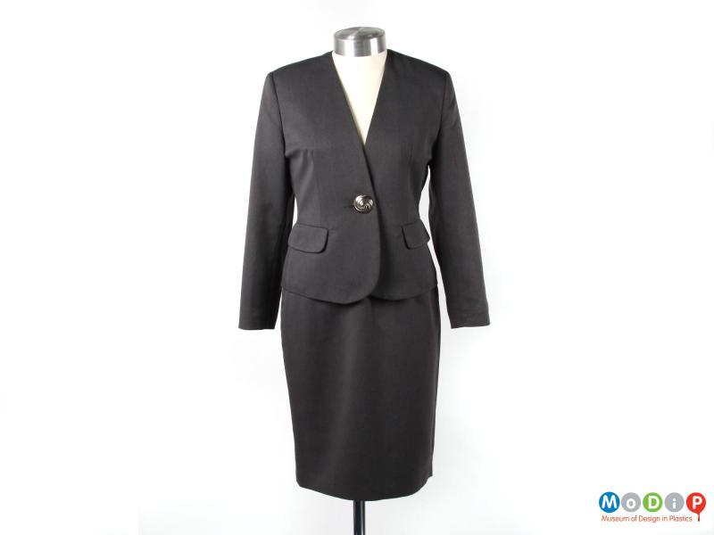 Front view of a skirt suit showing the collarless jacket.