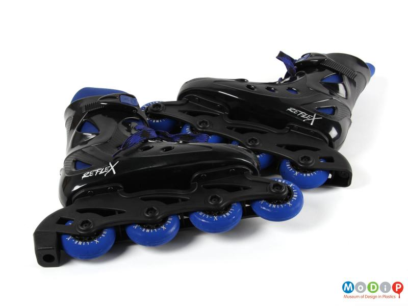 Side view of a pair of inline skates showing the small wheels.
