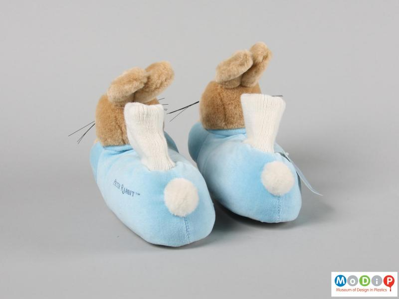 Rear view of a pair of slipper showing the pom-pom tail.