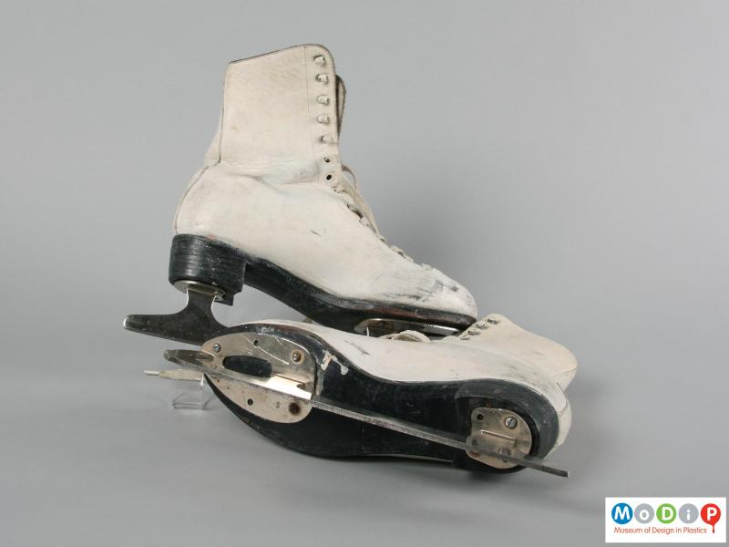 Underside view of a pair of ice skates showing the blades attached to the sole.