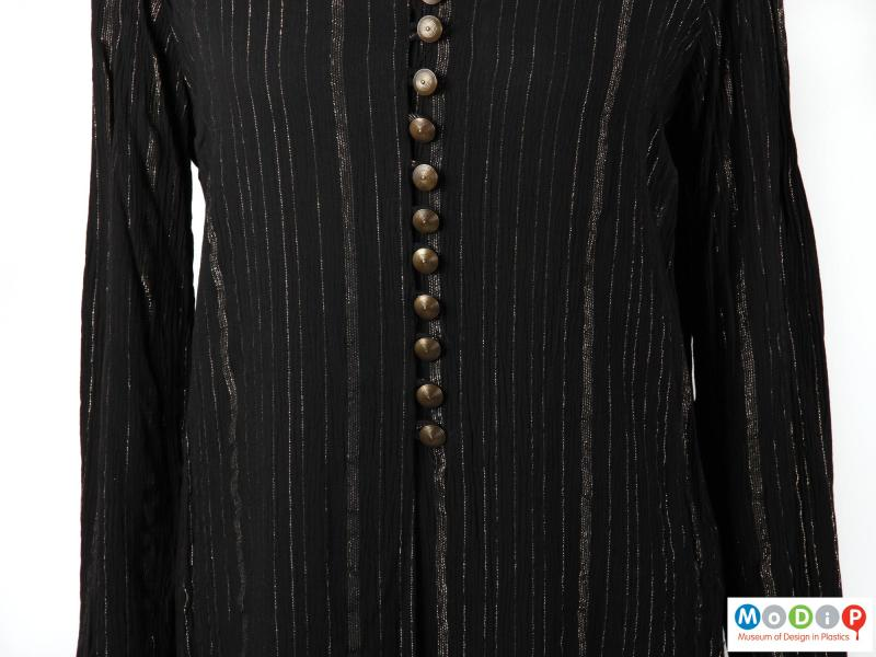 Close view of a blouse showing the fabric and buttons.