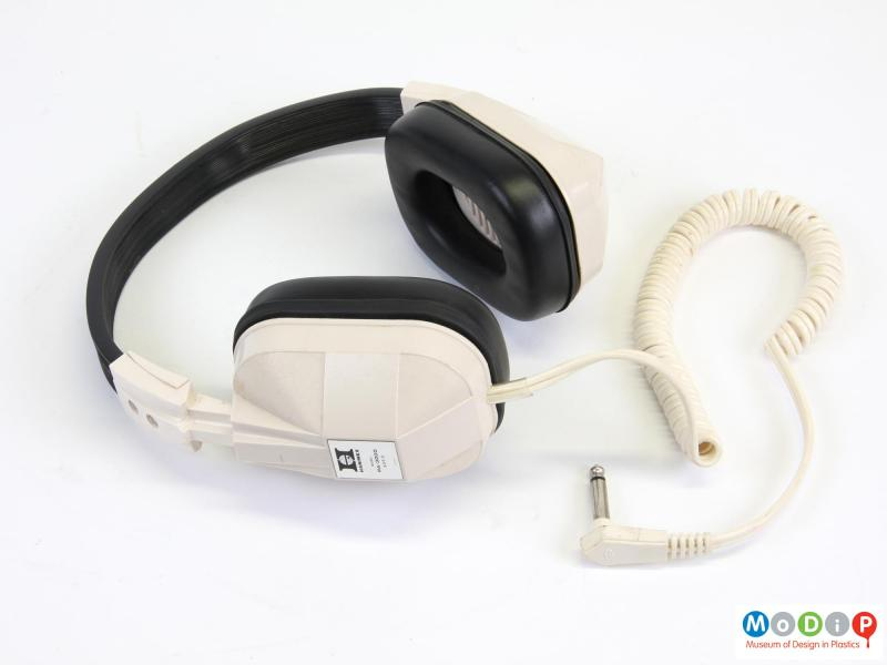 Side view of a pair of headphones showing the curled cable.