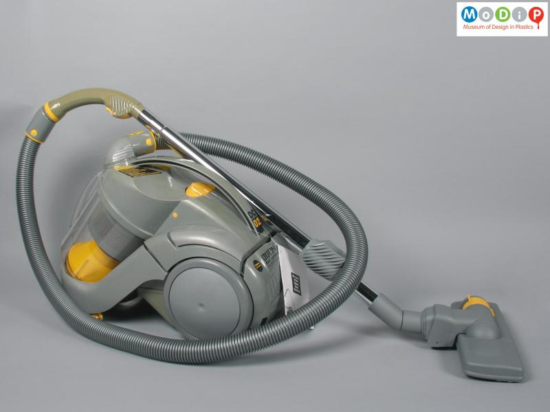 Side view of a vacuum cleaner showing the hose and carpet sweeper.