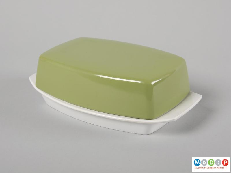 Side view of a butter dish showing the handles on the base.