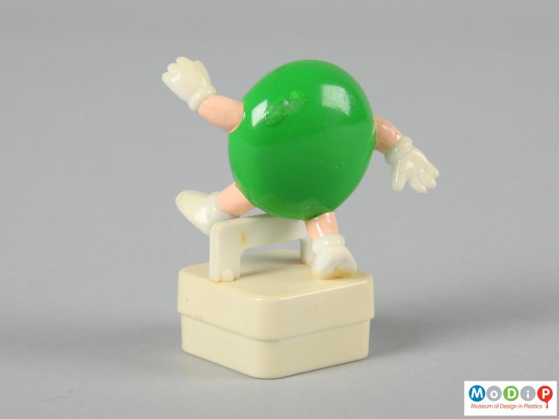 Side view of a green M&M figure showing the plain back.