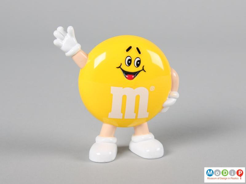 Front view of a yellow M&M figure showing the smiling face and the limbs.