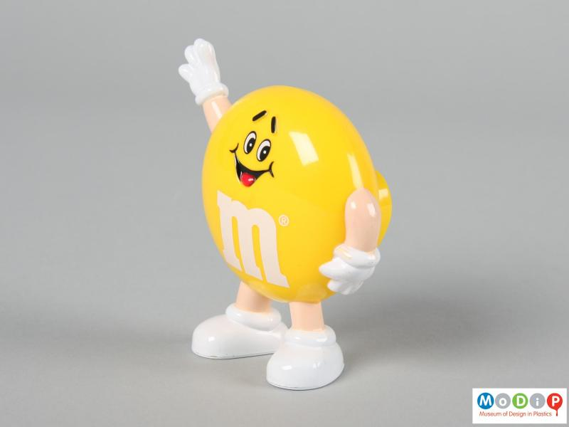 Side view of a yellow M&M figure showing one hand down by the figure's side.