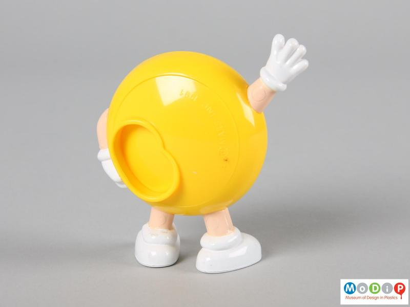 Rear view of a yellow M&M figure showing the back plate with a lipped hole on one side.