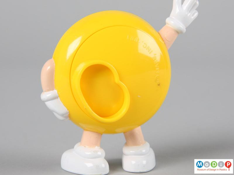 Close view of a yellow M&M figure showing the back plate closed.
