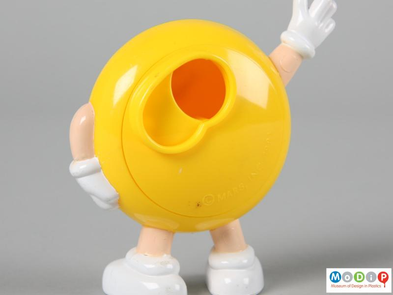 Close view of a yellow M&M figure showing the back plate open.