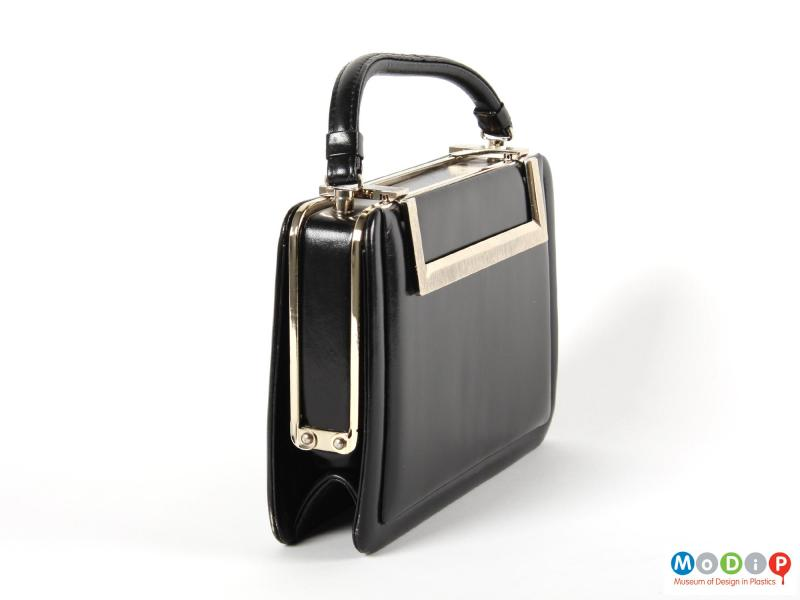 Side view of a handbag showing the metal hinge.