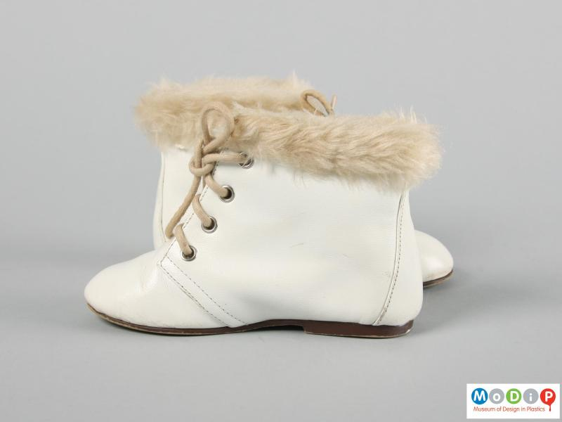 Side view of a pair of boots showing the fake fur trim.