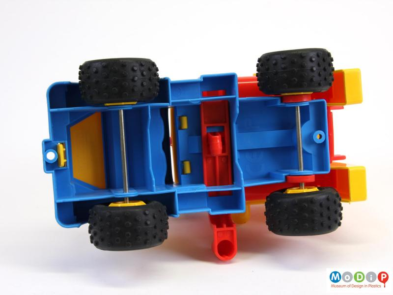Underside view of a toy truck showing the metal axles.