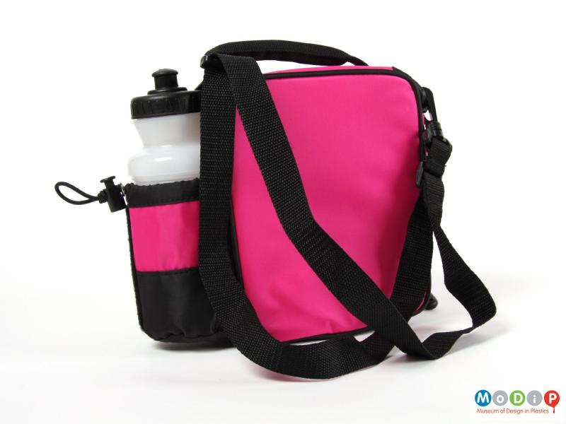 Rear view of a Thermos lunch tote showing the plain back and the pocket for the drink bottle (complete with drink bottle) on the side.