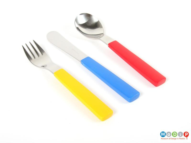 Top view of a cutlery set showing the primary colours of the handles.