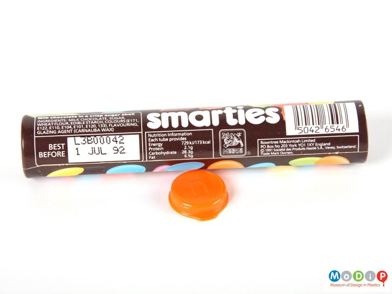 Side view of a Smarties tube showing the printed decoration and the inside of the lid.