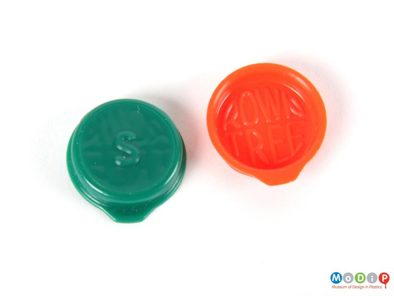 Top view of two Smarties lids showing the moulded inscriptions.