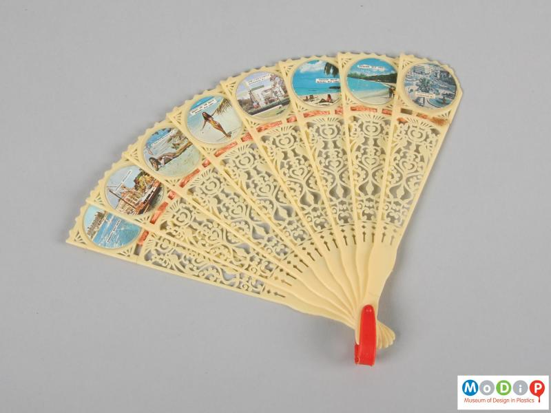 Front view of a hand fan showing the glued-on pictures.
