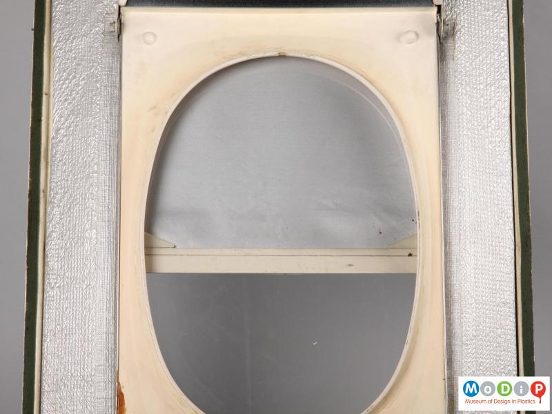 Close view of a Trident aeroplane window showing the clear viewing pane and surround with the integral blind pulled down.