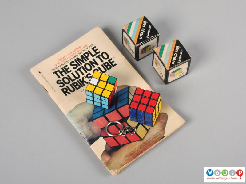 Top view of a puzzle key chain showing both puzzles, the boxes and the book.