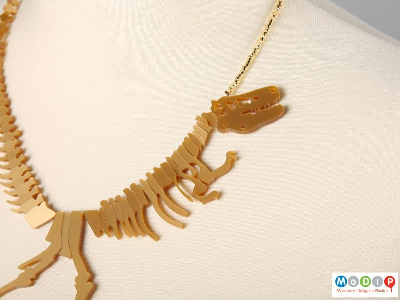 Close view of a Tatty Devine necklace showing the head and arms of the dinosaur.