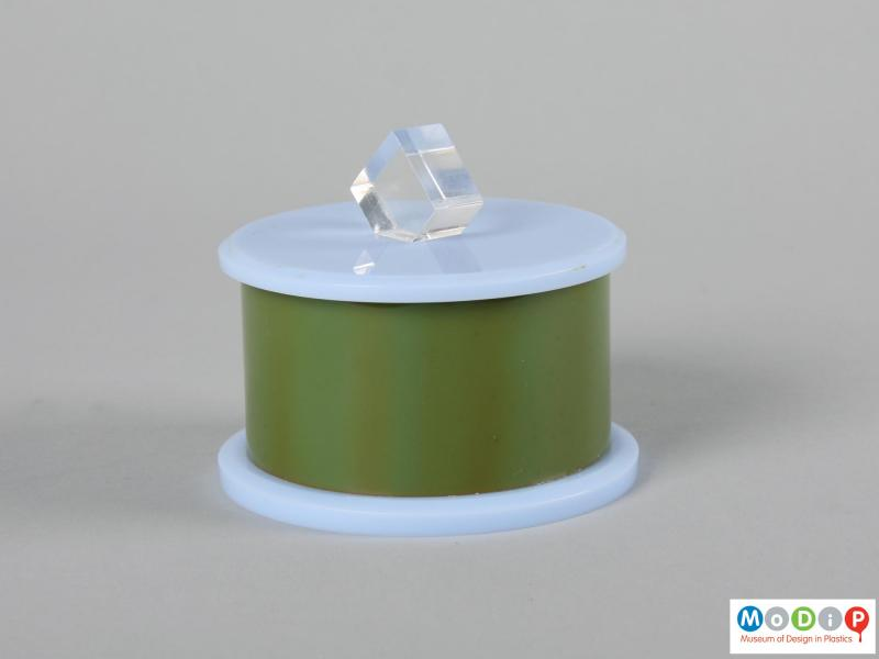 Side view of a trinket box showing the clear diamond shaped knob on the lid.
