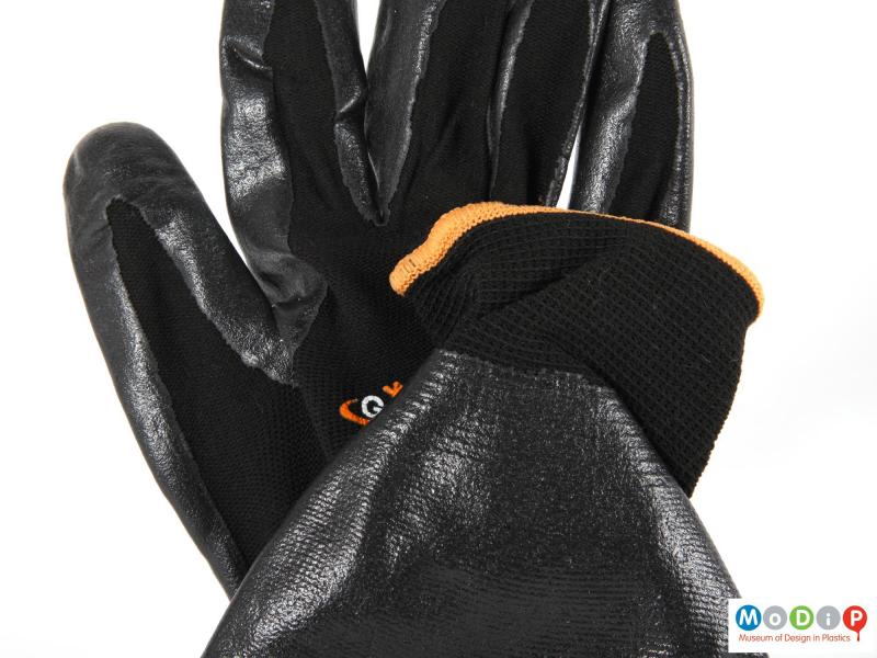 Close view of a pair of gloves showing the different material surfaces.