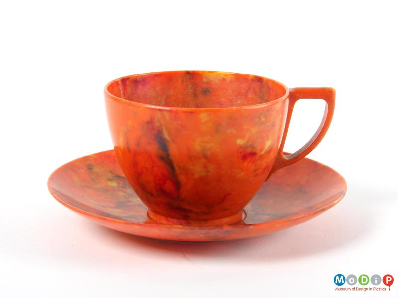 Side view of a cup and saucer showing the angular handle.