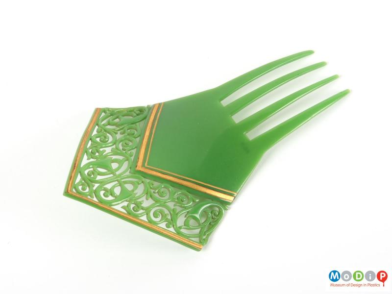 Front view of a back comb showing the gold coloured decoration.