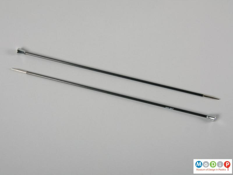Side view of a pair of knitting needles showing the plain shaft and metalised tip and head.