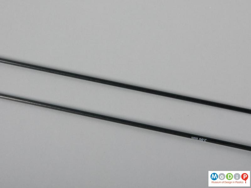 Close view of a pair of knitting needles showing the material.