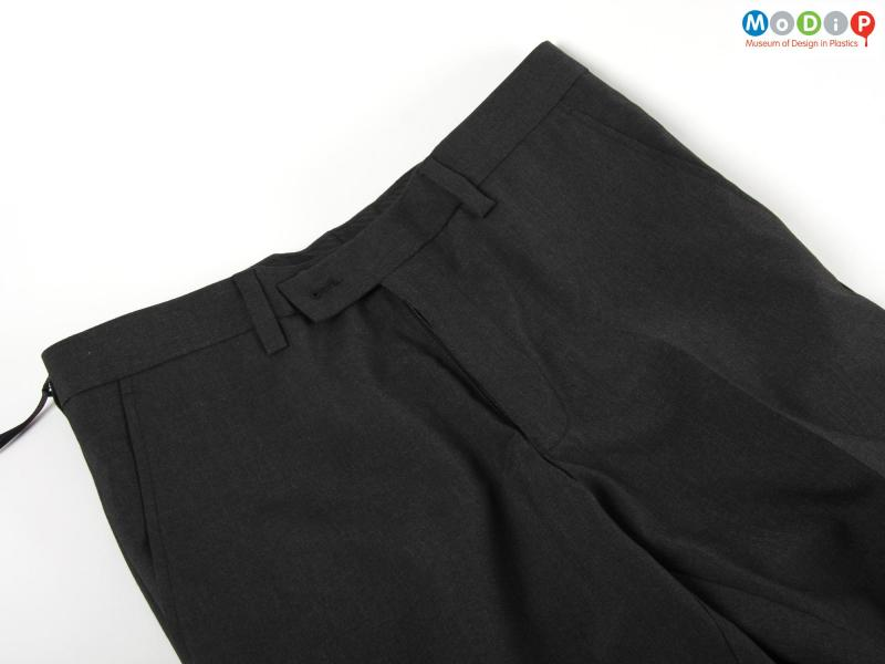 Close view of a pair of trousers showing the waist band.