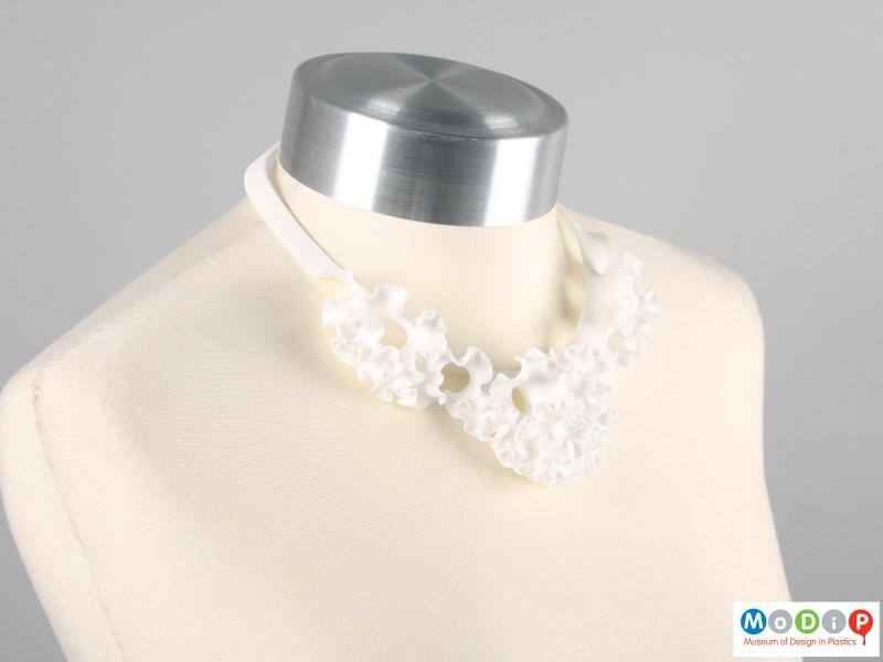 Side view of a necklace showing the ruffle design.