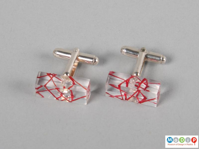 Side view of a pair of cuff links showing the clear material.