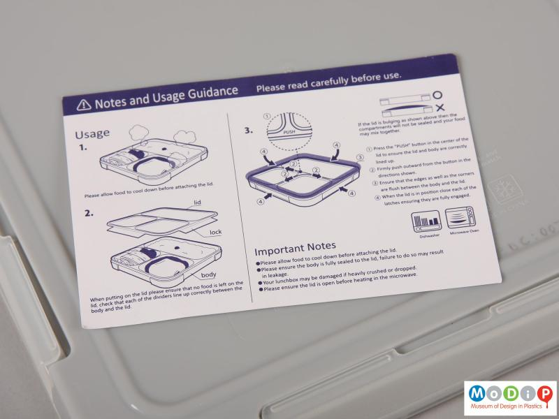 Close view of a lunch box showing instruction leaflet.