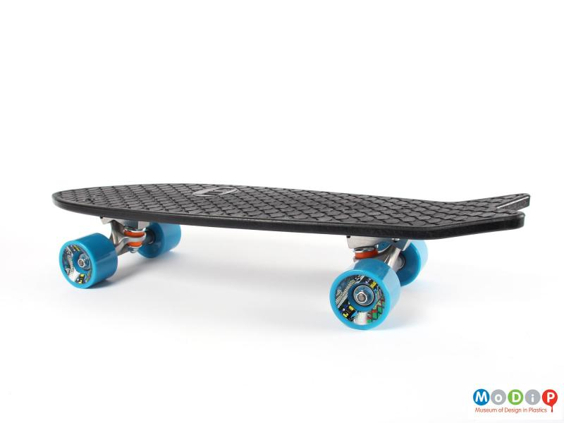 Side view of a skateboard showing the blue wheels.