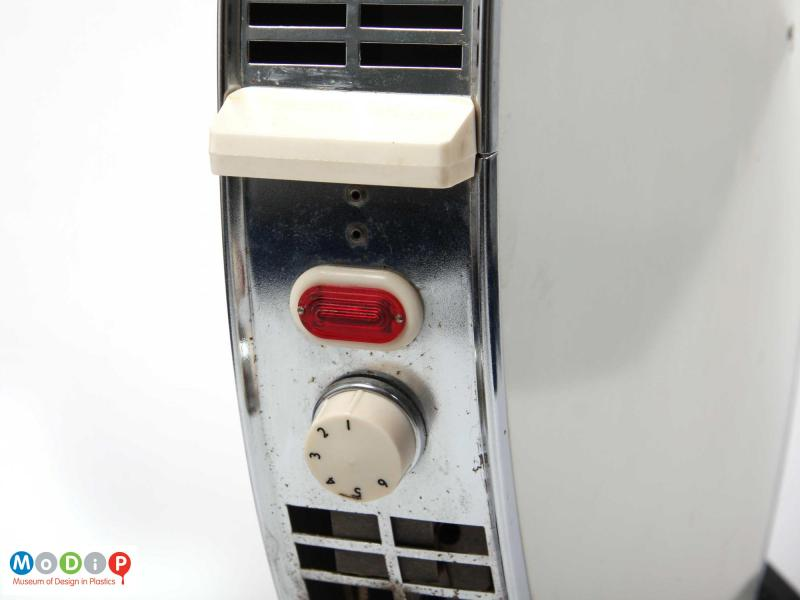 Close side view of a Sofono electric heater showing the control dial and the handle on one side.
