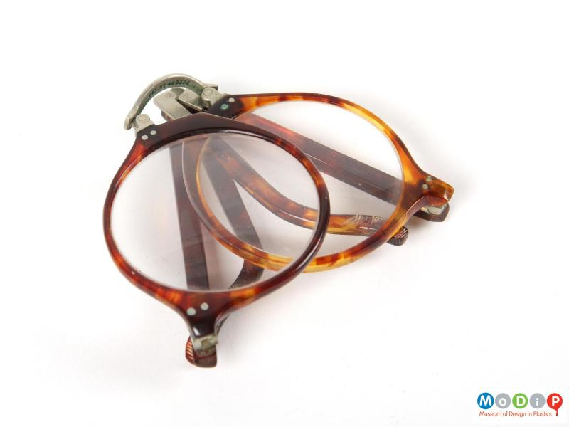 Front view of a pair of folding glasses showing the frame beginning to be unfolded.