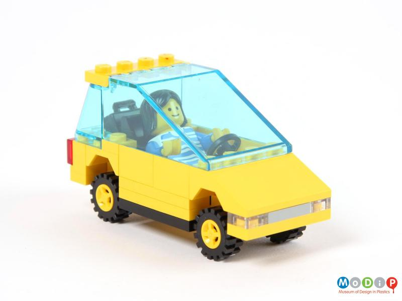 Side view of a toy car showing the figure in the driver's seat.