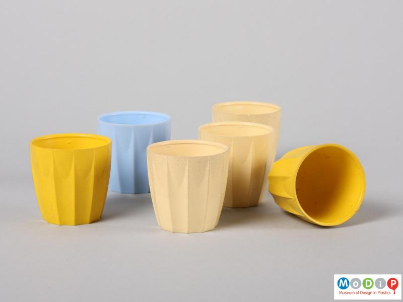 Side view of six nBware egg cups showing the distinct moulded ribbing down the side of the cups.  One cup is on its side to reveal the inside surface.