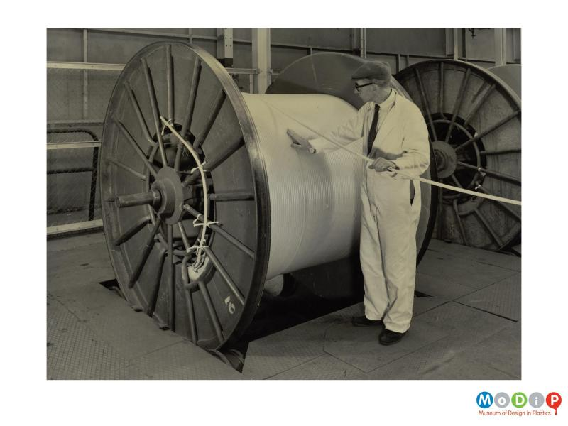 Scanned image showing a male worker feeding coiling a cable onto a large drum.