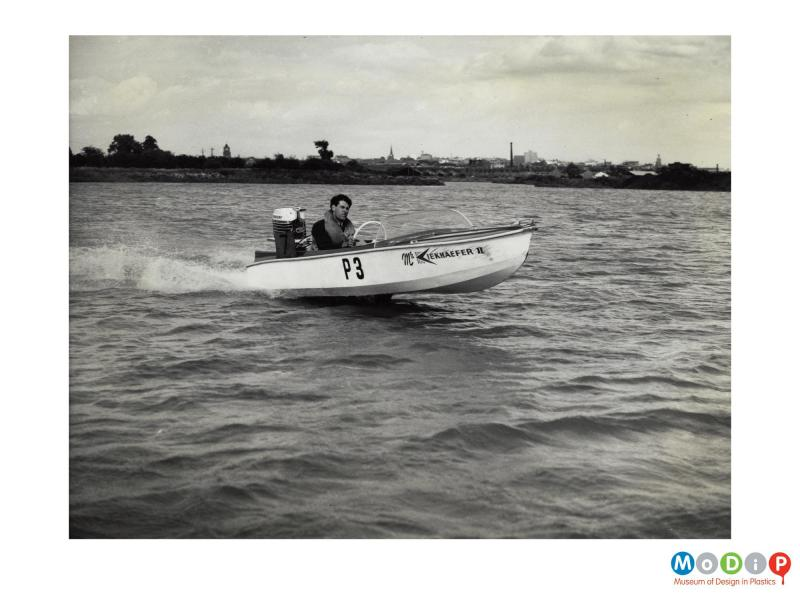 Scanned image showing small motor boat on the water.