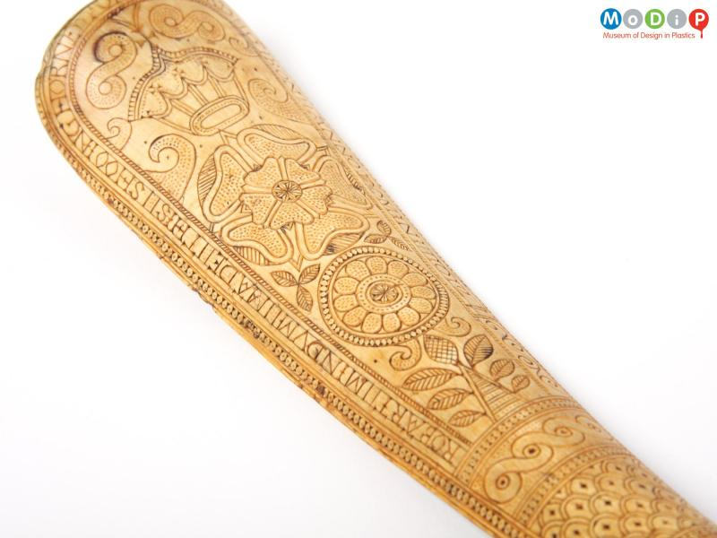 Close view of a shoe horn showing the carving.