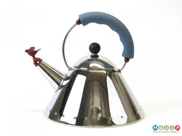 Side view of a kettle showing the trimmed handle and bird shaped whistle.