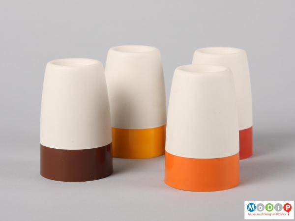 Side view of four Tupperware egg cups showing the plain sides of the cream cover and coloured bases of the cups.