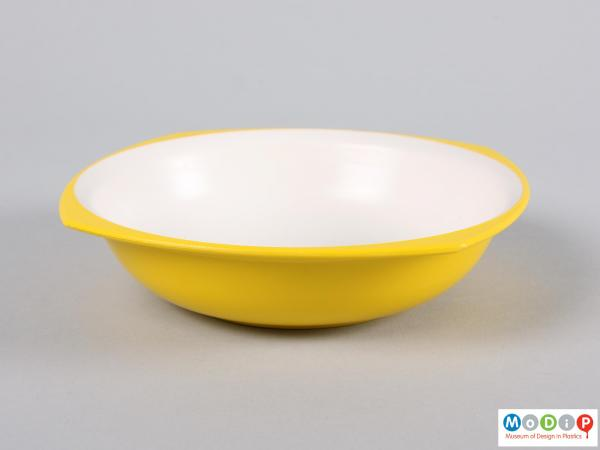 Side view of a bowl showing yellow outer and white inner surface.