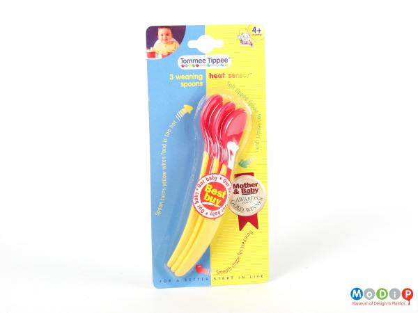 Front view of a packaged set of Tommee Tippee spoons showing the yellow handles and red bowls.