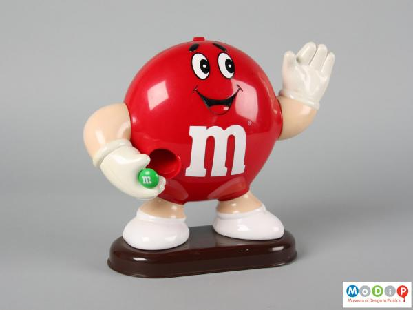 Front view of a red M&M figure showing the smiling face and the limbs.