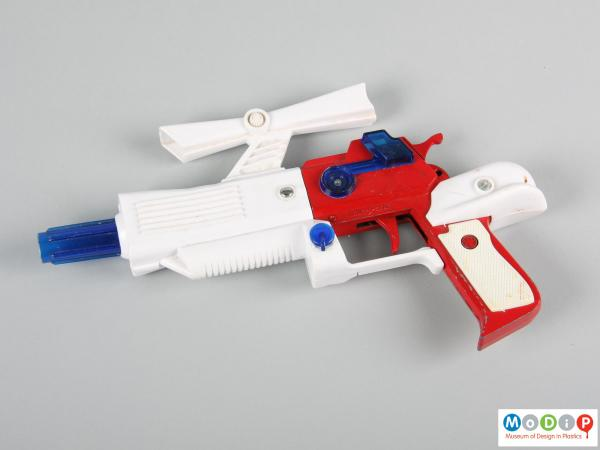 Side view of a toy gun showingthe red metal handle and white and blue plastic attachments.